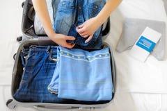 女性手特写镜头包装一个手提箱 旅途开始! 免版税库存图片