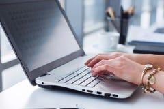 女性手特写镜头照片有研究便携式计算机的辅助部件的在一个现代办公室,使用键盘 免版税库存图片