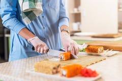 女性手特写镜头视图在烹调传统日本寿司卷的手套的切开用刀子在厨房里 免版税库存照片