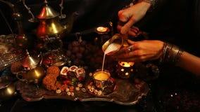 女性手用东方jewelery倾吐的茶到杯里 传统摩洛哥的甜点 杯番红花Masala牛奶茶 影视素材