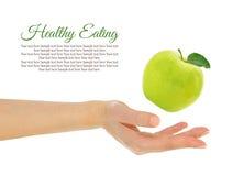 女性手用新鲜的绿色苹果 免版税库存图片