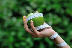 女性手用绿色苹果和测量的磁带 库存图片