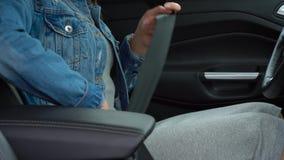 女性手紧固汽车安全安全带,当坐在车里面时在驾驶前 股票视频