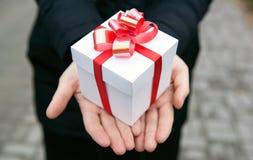 女性手给您一个礼物盒 免版税库存照片