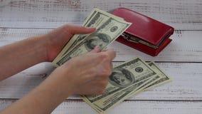 女性手考虑一百美元票据 金钱在桌上下降,说谎一个红色钱包 股票录像