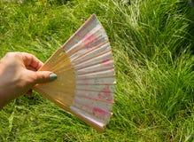 女性手藏品打开在草背景的一个竹爱好者,复制空间 免版税库存图片