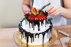 女性手装饰一个白色奶油色蛋糕用果子,特写镜头 库存照片