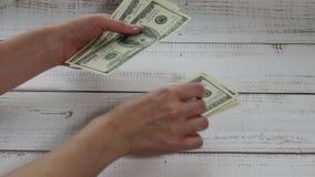 女性手计数一百美元金融法案 金钱在桌上下降 影视素材