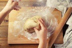 女性手采取烘烤的饼或者薄饼的面团从碗自创准备的食物 顶视图 土气的背景 免版税库存图片