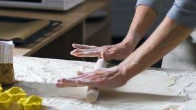 女性手铺开与辗压别针的面团在面粉盖的木桌上 股票录像
