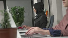 女性手键入在键盘的,特写镜头 黑hijab的女孩在背景中 办公室,事务,工作,妇女 股票录像