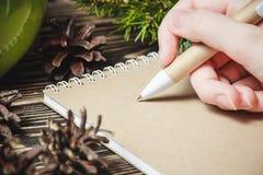 女性手,笔,笔记本,在圣诞节装饰背景 免版税图库摄影