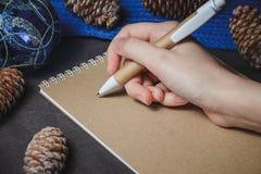 女性手,笔,笔记本,在圣诞节装饰背景 免版税库存照片