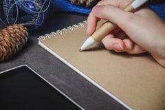女性手,笔,笔记本,在圣诞节装饰背景 免版税库存图片
