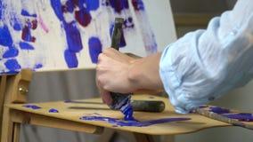 女性手紧压在管外面蓝色油漆遗骸在一个木画架的 影视素材