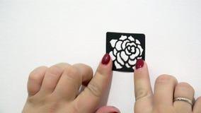 女性手黏附一个黑屏幕以玫瑰的形式在一个白色基地 股票录像