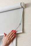 女性手whith修指甲关闭滚动快门和窗帘在窗口 图库摄影