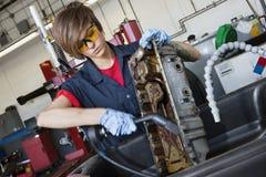 年轻女性技工与在车机器零件的气焊枪一起使用在汽车修理店 库存照片