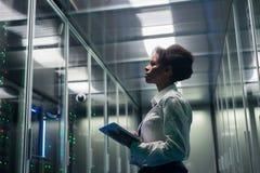 女性技术员在一种片剂在数据中心工作 免版税图库摄影