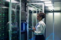 女性技术员在一种片剂在数据中心工作 免版税库存图片