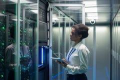女性技术员在一种片剂在数据中心工作 图库摄影