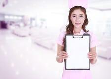 女性护士展示空白剪贴板在医院 图库摄影