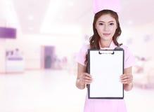 女性护士展示空白剪贴板在医院 免版税图库摄影