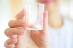 女性护士或医生拿着药片在医疗杯子的白色褂子制服的 医疗保健、医学和专业专家 免版税库存图片
