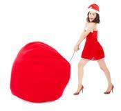 年轻女性拉扯与圣诞节衣服的一个重的礼物袋子 库存照片