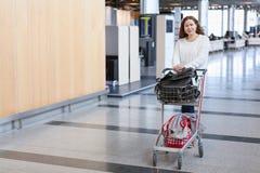 女性拉扯的行李手车在机场大厅里 免版税库存照片