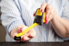 女性拿着一卷黄色测量的磁带 库存照片