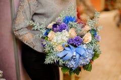 女性拿着与蓝色和白色八仙花属、米黄玫瑰和多汁植物的花束 库存图片