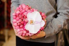 女性拿着与许多小桃红色玫瑰和一朵大白色兰花的花束 库存照片