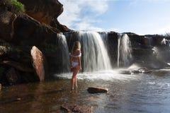 女性探索的和享用的瀑布和岩石水池本质上 库存图片
