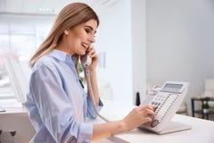 女性接待员谈话在电话在旅馆检查 免版税图库摄影