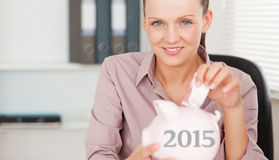 女性插入的金钱的综合图象在存钱罐中 免版税库存图片