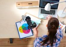 女性摄影师坐有膝上型计算机的书桌 库存图片