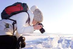 女性摄影师射击冬天风景画象在冻贝加尔湖旁边的 冬天旅游业在俄罗斯 库存照片