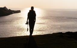 女性摄影师背包徒步旅行者剪影前面射击了在m顶部 库存照片