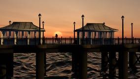 女性摆在沿海地带码头的日落 库存图片