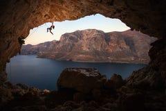 女性攀岩运动员剪影峭壁的在洞 免版税库存图片