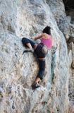 年轻女性攀岩运动员背面图峭壁的 图库摄影