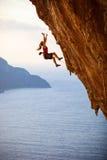 女性攀岩运动员落峭壁 库存图片