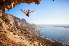 女性攀岩运动员落峭壁 免版税图库摄影