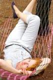 年轻女性放松在吊床 免版税库存图片