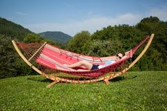 年轻女性放松在吊床 库存照片