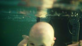 女性教练员或母亲教一点todler潜水在水下 在水上拿着他,透湿他的头和 股票录像