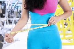 女性教练员特写镜头测量她的肚子 库存图片