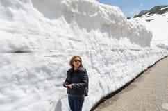 女性旅客和雪墙壁在日本阿尔卑斯馆山kurobe高山路线 图库摄影