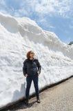 女性旅客和雪墙壁在日本阿尔卑斯高山馆山的kurobe 免版税库存图片